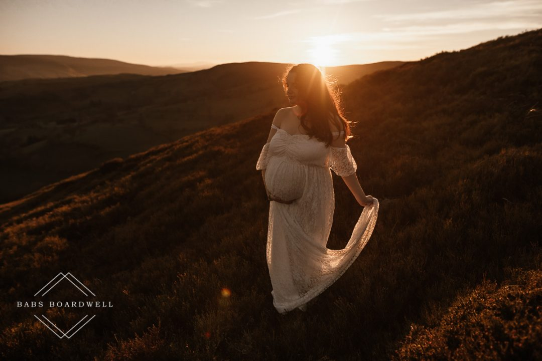 mum-to-be wearing a white dress in the hills at sunset by North Wales Maternity Photographer