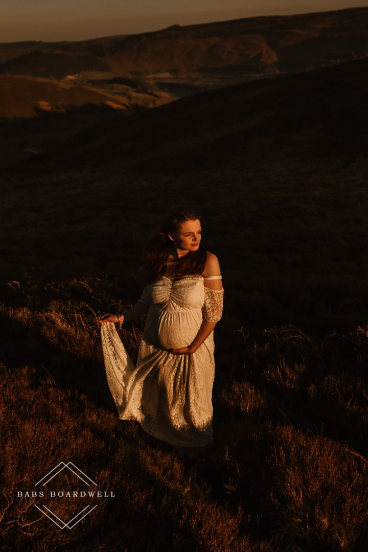 pregnant woman holding the hem of her with dress during sunset by North Wales Maternity Photographer