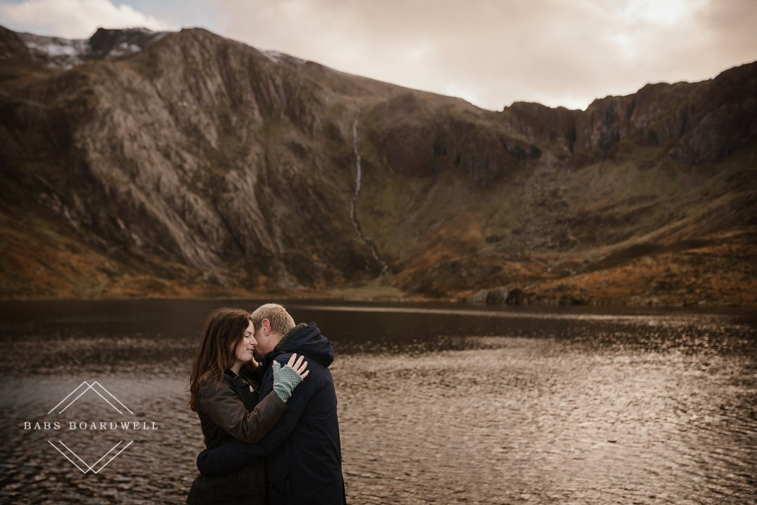 couple sitting on rocks with their backs to one another during their Ogwen Valley Couple Portrait