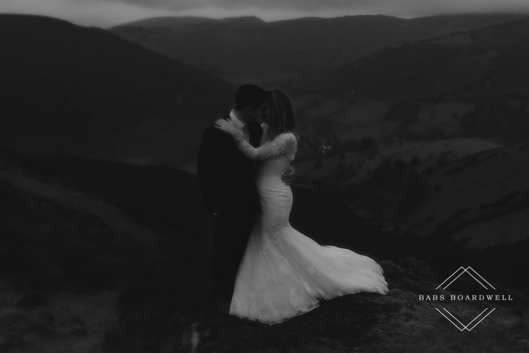 black and white image of bride and groom wearing their wedding outfits on a gloomy foggy day
