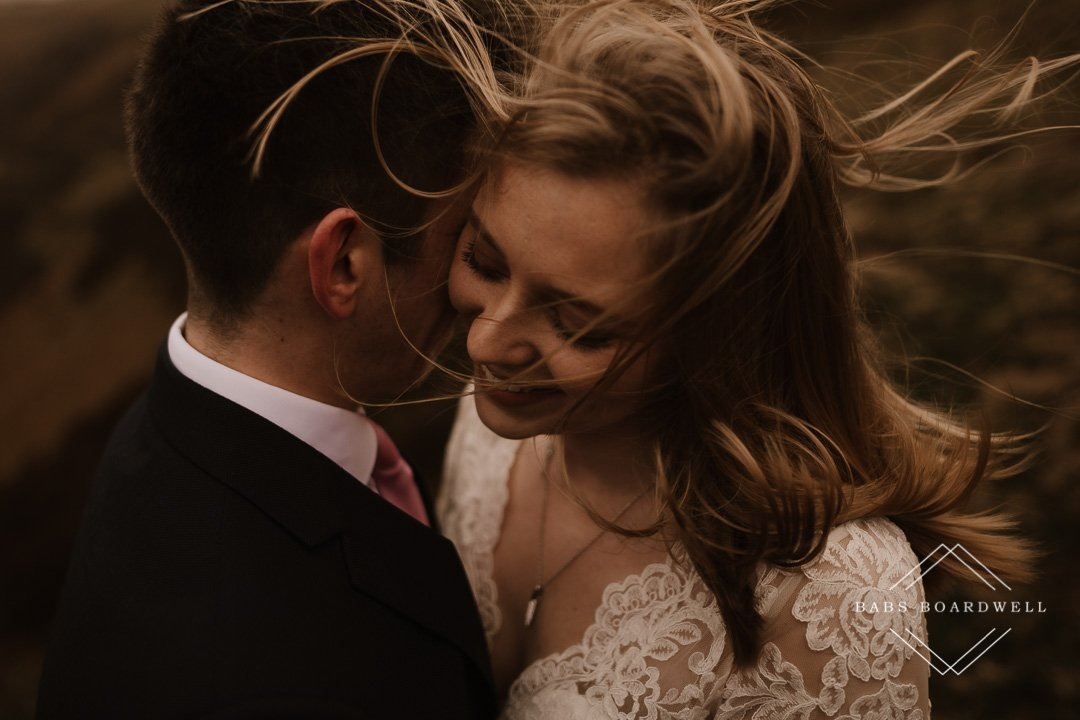 close-up of bride with the wind ruffling her hair while she's smiling
