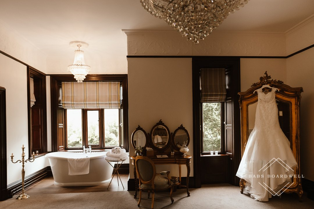 one of the bridal suites with a wedding dress hanging on the wardrobe during a romantic wedding at Tyn Dwr Hall