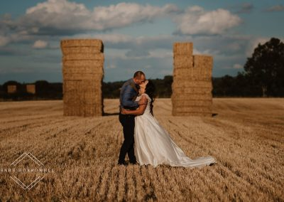 bride and groom kissing in-between stacks of straw during their summer wedding in North Wales