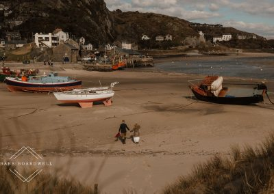 bride and groom walking across the beach in Barmouth with boats in the background