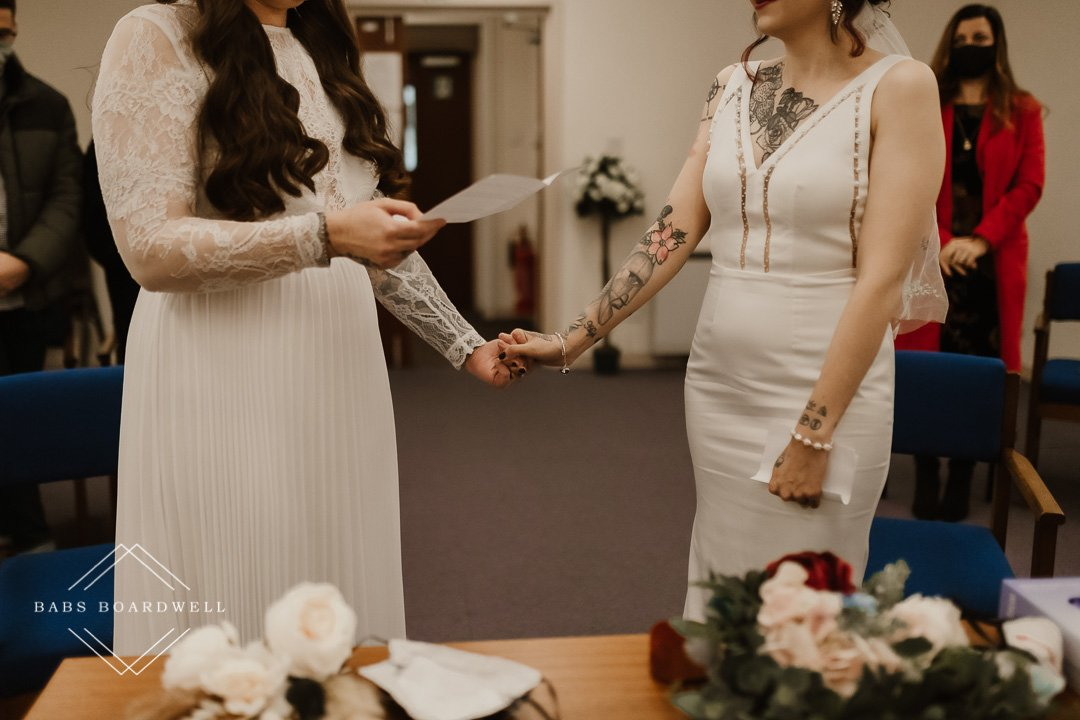 lesbian brides holding hands during same-sex wedding service at Dolgellau Registry Office